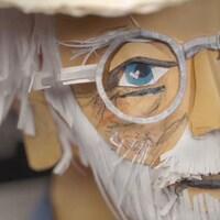 Une sculpture en papier d'un homme âgé.