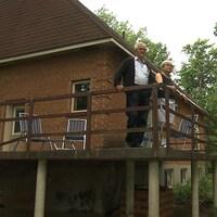 Un couple sur un balcon arrière d'une petite maison brune.