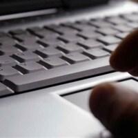 Une main sombre devant un clavier d'ordinateur portable.