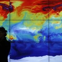 Une femme devant une carte numérique du monde qui montre les variations de températures.