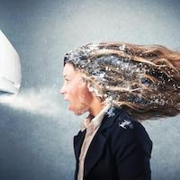 Une femme debout devant un climatiseur soufflant de l'air très froid.