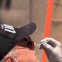 Une infirmière qui porte masque, visière et gants prend un prélèvement dans le nez d'un homme.