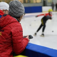 L'entraîneuse Martine Dupont regarde un patineur sur la glace.