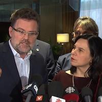 Un homme et une femme debout dans une mêlée de presse.