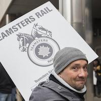 Un employé du CN porte une pancarte à l'extérieur du siège social du CN à Montréal, le mardi 26 novembre 2019.