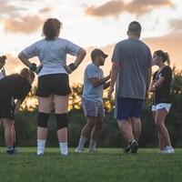 Les deux entraîneurs donnent des consignes à leurs joueuses sur un terrain de football.