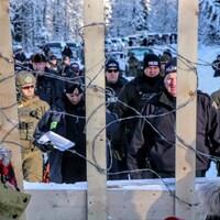Des agents de la GRC négocient avec des membres des Premières Nations derrière un fil barbelé.