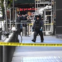 Un démineur en uniforme marche près du Time Warner Center.