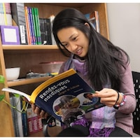 Une femme regarde le cahier, dont la page de couverture montre des images du Grand Nord.