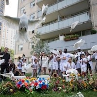 des colombes volent dans les airs devant un immeuble à Toronto et des gens