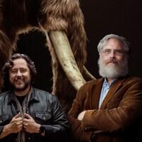 Les cofondateurs de Colossal, Ben Lamm et George Church prennent la pose devant une illustration de mammouth laineux.