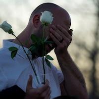 Un homme porte sa main à son visage. Il tient des roses blanches dans l'autre main.