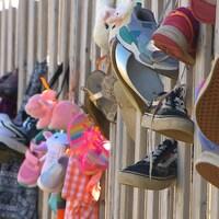 Des souliers d'enfants accrochés à une clôture.