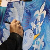 Une personne écrit un mot dans une œuvre collective lors de la soirée de commémoration du 2e anniversaire de l'attentat à la Grande mosquée de Québec