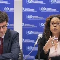 Un homme et une femme assis en conférence de presse avec, en fond de scène, le logo de la  la Commission des droits de la personne et des droits de la jeunesse