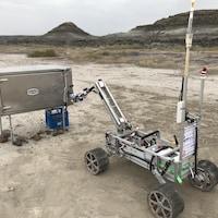 Un robot muni d'un bras et monté sur quatre roues tente d'ouvrir une boîte en métal.