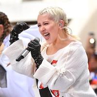 La femme chante dans un micro, le bras droit en l'air.