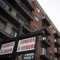 Pancarte indiquant des condos à vendre et à louer avec un édifice en arrière-plan.