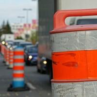Des cônes orange délimitant une zone de travaux à Montréal, avec une file de véhicules à droite.