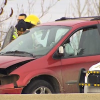 Des policiers et pompiers examinent une fourgonnette à l'avant violemment accidenté.