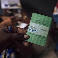 Un électeur montre une carte sur laquelle on peut lire «A VOTÉ».