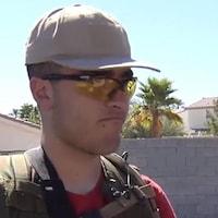 Un jeune homme portant une casquette et une veste pare-balles.