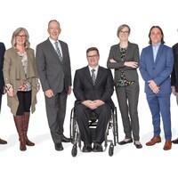Les sept conseillers posent de plain-pied devant un fond blanc.