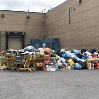 De nombreux sacs remplis de canettes et de bouteilles vides devant une porte de garage. C'est le jour.