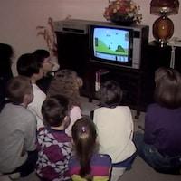 Un groupe d'enfants sont tournés vers un écran de téléviseur sur lequel se déroule une partie du jeu Mario Bros sur console Nintendo.