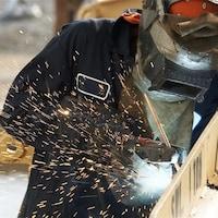 Un travailleur utilise une pince d'une main et de l'autre une soudeuse. Il travaille à joindre deux pièces ensemble.