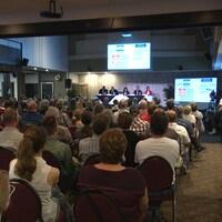 Une foule de citoyens écoutent une présentation lors d'une consultation publique.
