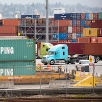 Des conteneurs empilés et des camions garés dans le port de Vancouver.