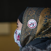 Une femme masquée porte un voile sur lequel est épinglé un macaron contre la loi 21.