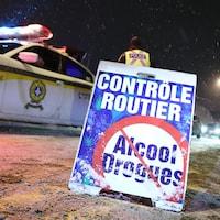 Une affiche annonce un contrôle routier. Une voiture de police est stationnée derrière.