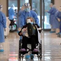 Un infirmier pousse le fauteuil roulant d'une dame âgée dans le corridor d'un hôpital.
