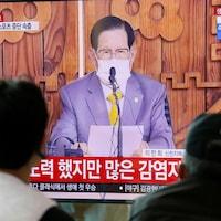 Dans un écran de télévision, un homme avec un masque assis derrière un micro.