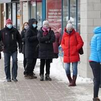 Des gens attendent en file à l'extérieur d'un commerce rue Saint-Germain, à Rimouski. Tous portent un couvre-visage.