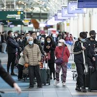 Des passagers portent un masque à l'aéroport de Vancouver.