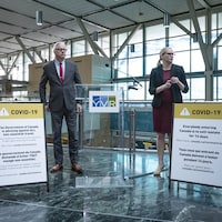 Craig Richmond, le PDG de l'aéroport de Vancouver, et une femme prêt à faire une conférence de presse.