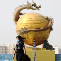 Une femme masquée marche devant une sculpture montrant un serpent enlaçant une sphère.