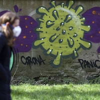 Une femme masquée passe devant un mur de pierre sur lequel est dessiné un graffiti représentant un virus.