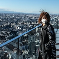 Une femme masquée surplombe Tokyo du haut d'une tour.