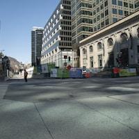 Une seule personne marche sur la rue Sainte-Catherine au centre-ville de Montréal en pleine journée.