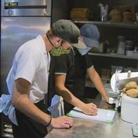 Deux employés d'un restaurant discutent dans la cuisine en portant chacun un masque.
