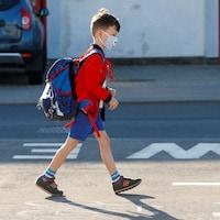 Un enfant en pantalon court porte un masque sur le visage. Il marche et a un sac à dos.