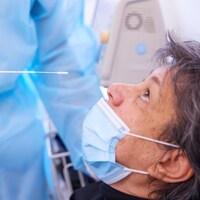 Une personne âgée lève les yeux vers une tige qui servira à prélever un échantillon dans sa narine, le 26 novembre 2020 à Meyrin, en Suisse.