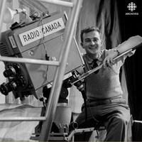 Un caméraman perché sur sa caméra derrière un échafaud sur un plateau de tournage.