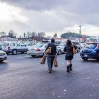 Deux femmes marchent dans un stationnement d'un centre commercial.