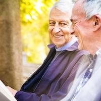 Deux hommes âgés assis sur un banc de parc.