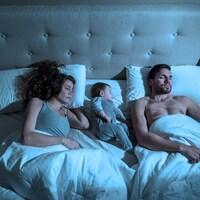 Un couple dort avec son bébé dans un lit.